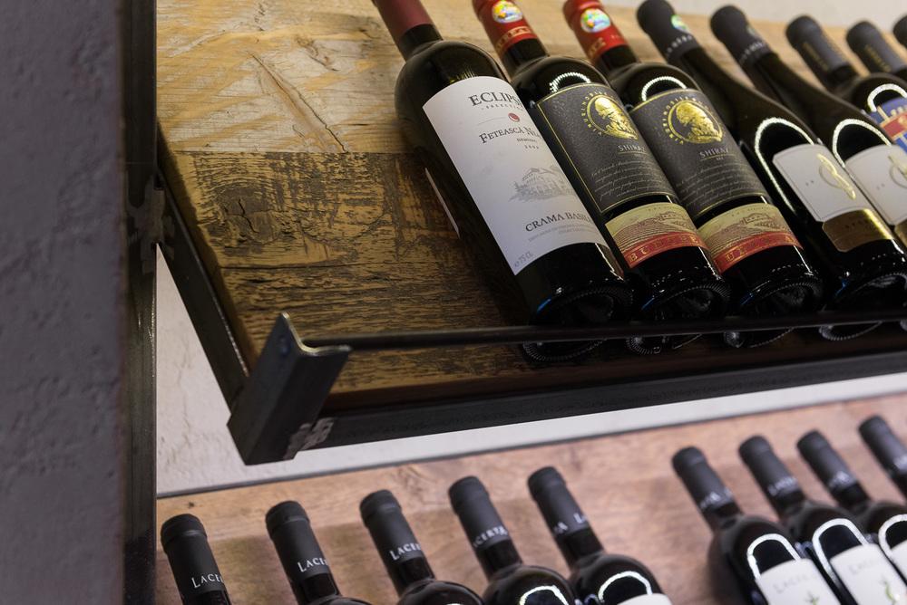 detaliu rafturi metalice de vin cu polite din brad antic